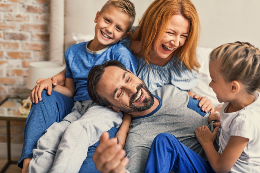 young smiling family of four having fun while lying on bed