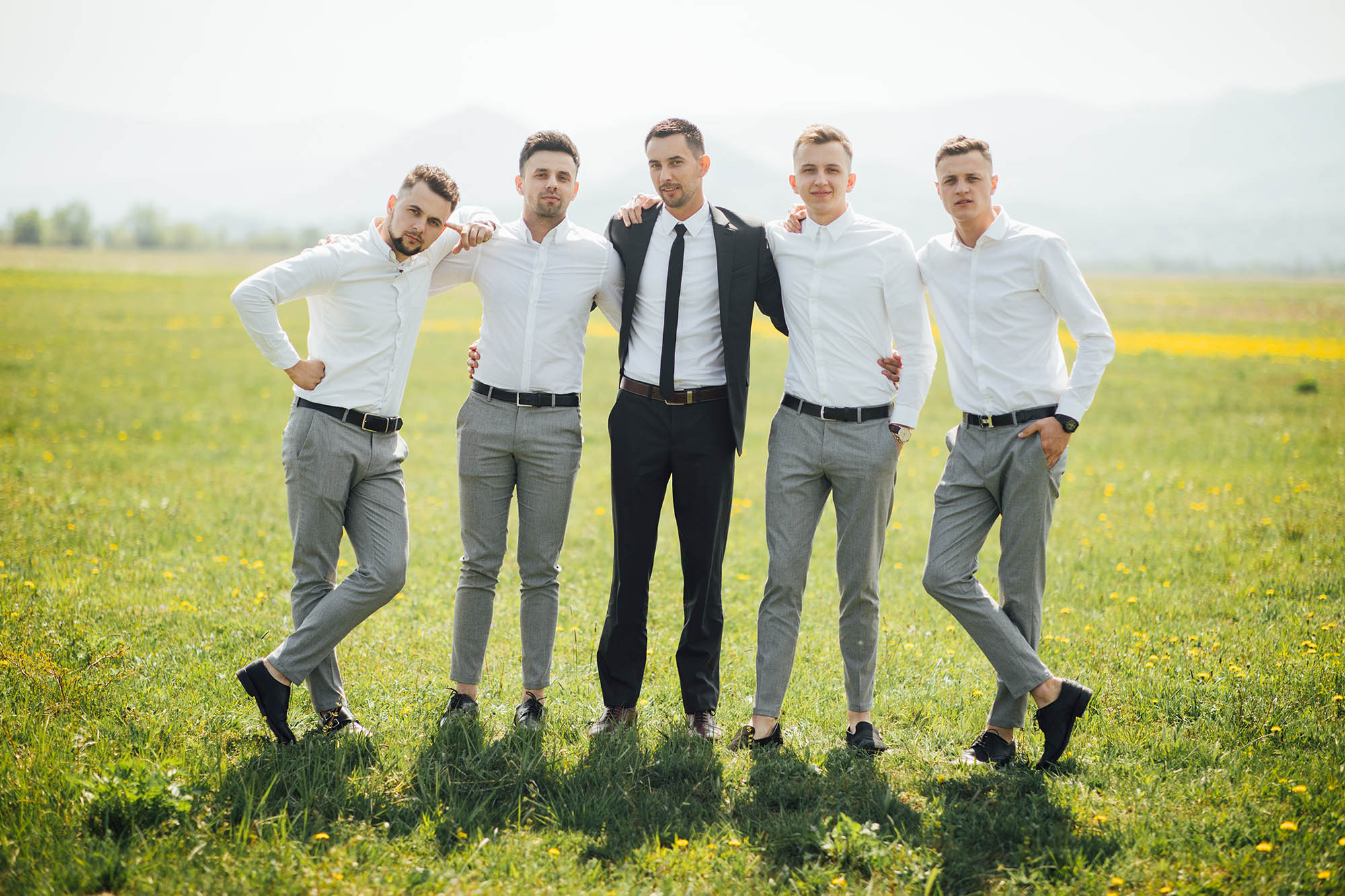 Groomsmen and groom posing outdoors on the wedding day