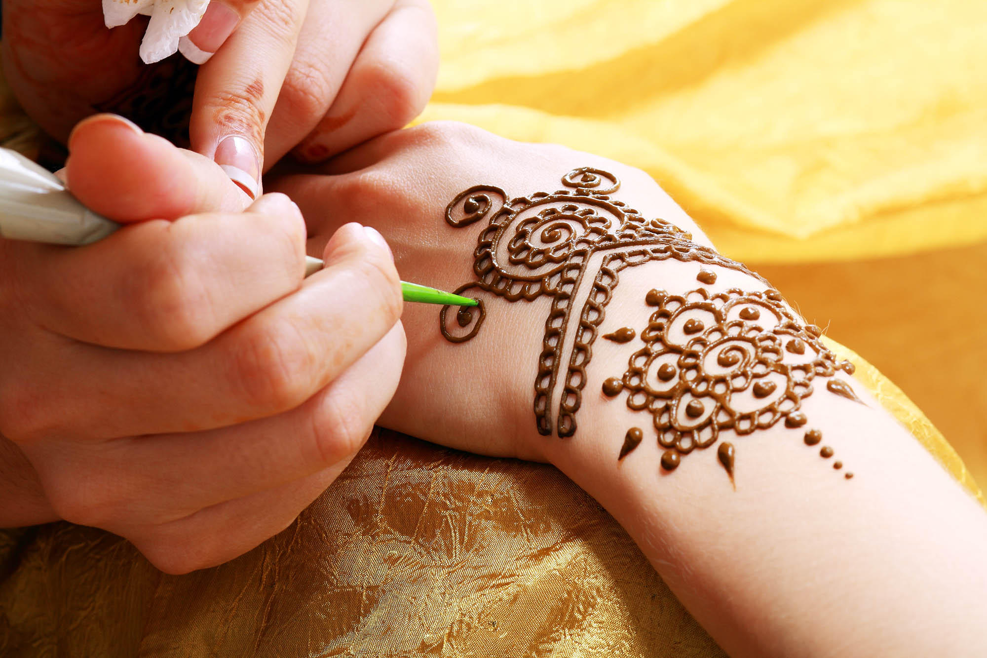 henna being applied to hand over golden fabric