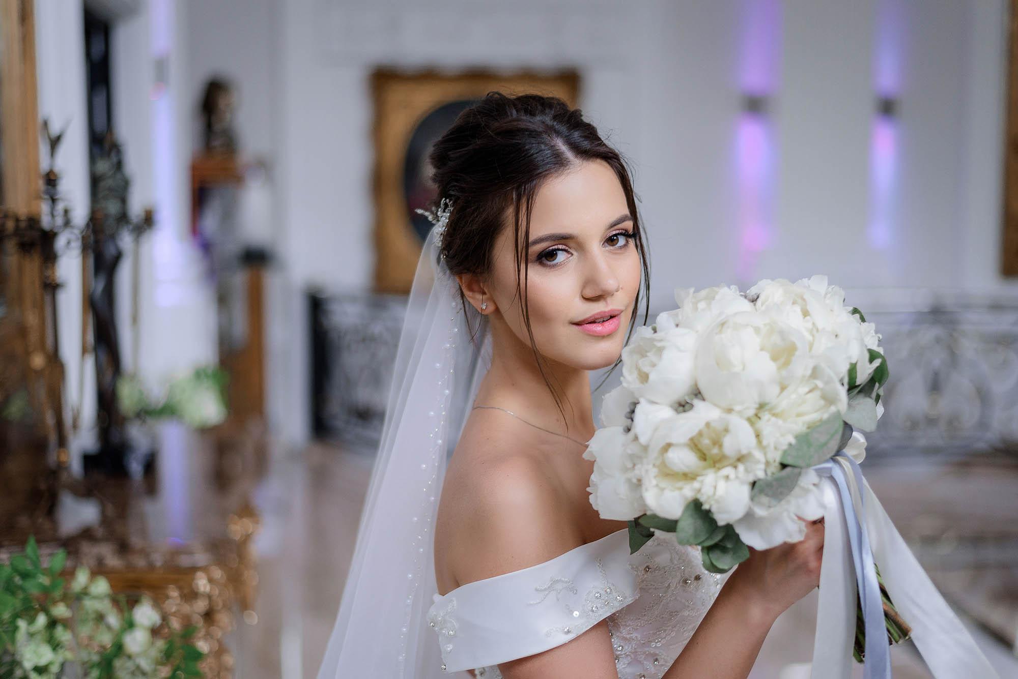 Beautiful brunette caucasian bride is holding bouquet