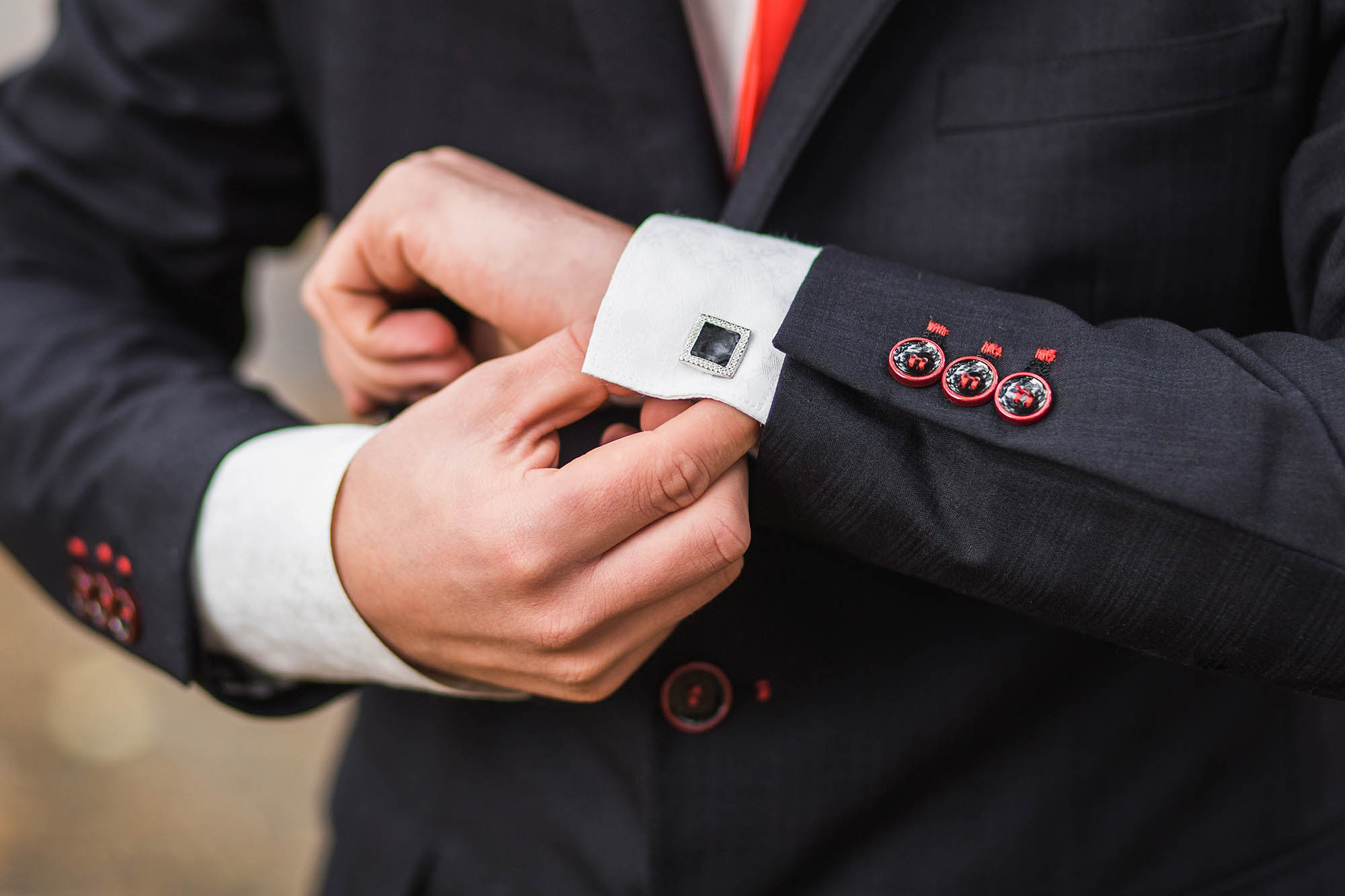 Elegant young fashion man looking at his cufflinks while fixing them