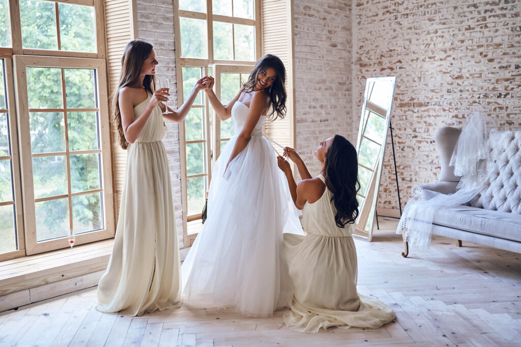 Full length of two attractive young women adjusting a wedding dress on a