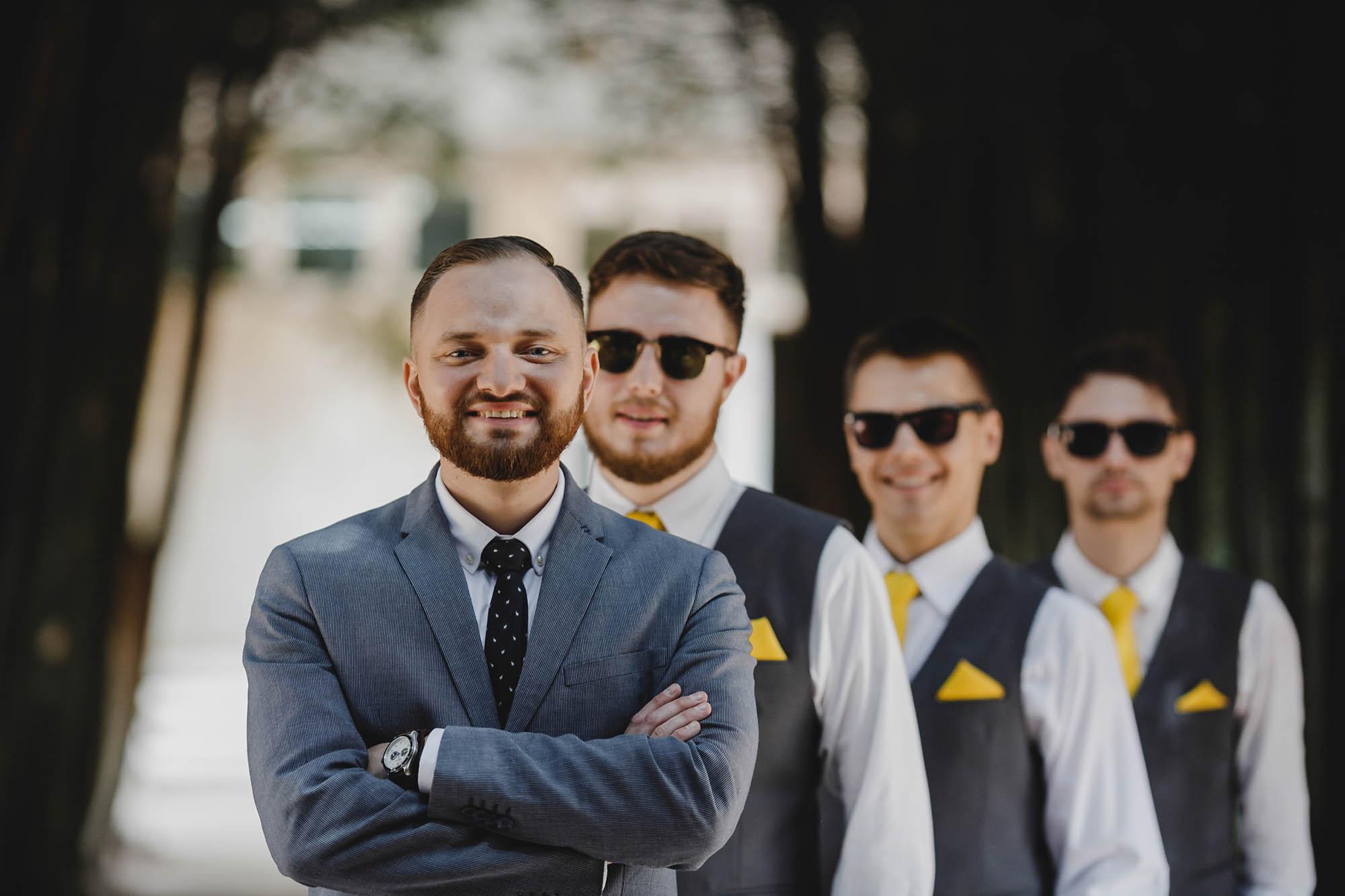 Groomsmen in black sunglasses with yellow ties stand behind bearded groom