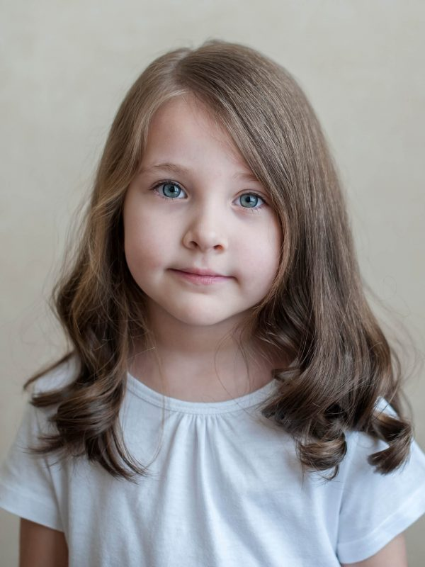 Portrait of little beautiful brunette girl smiling looking at camera over background